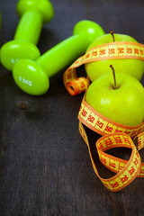 Apple,dumbbells and measuring tape