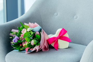 close up view of wrapped bouquet of flowers and heart shaped gift box with ribbon on armchair, mothers day concept