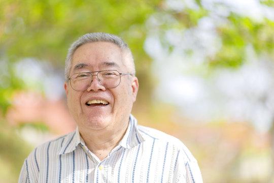 自然の緑背景とシニア日本人男性