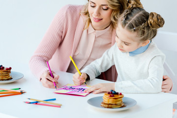 portrait of mother and daughter making greeting postcard together at table