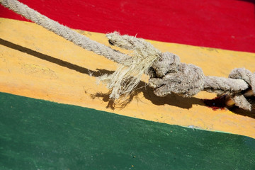 Typical Rastafarian Caribbean colors of red, green & yellow, painted on wood, with a nautical knot in front, St George, Grenada.