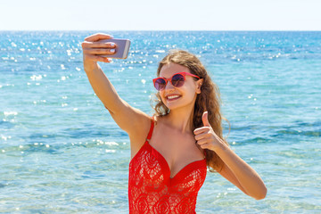 young girl having fun taking smartphone selfie pictures of herself. travel holidays. happy young woman giving hand sign thumbs up on beach