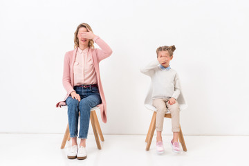 mother and daughter sitting on chairs and covering eyes with hands on white