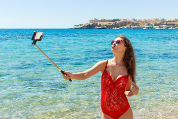 Summer beach vacation girl taking fun mobile selfie photo with smartphone. Girl wearing red sunglasses posing for selfie