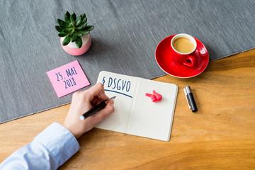 DSGVO geschrieben auf Notizblock mit Hand auf Schreibtisch von oben