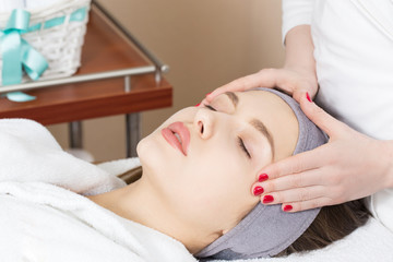 Facial massage for a beautiful girl in a spa salon