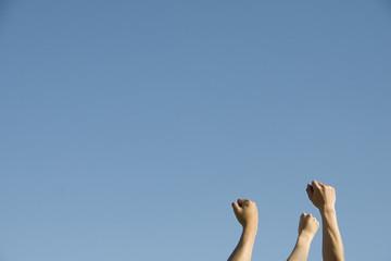 空に向けて突き上げた若者たちの手