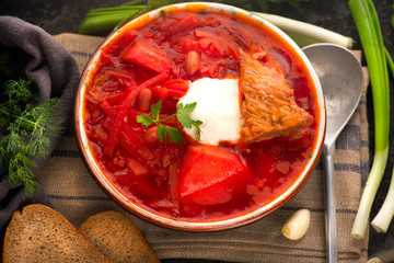 Traditional Ukrainian russian borscht. Plate of red beet root soup borsch on black rustic table. Beetroot soup top view. Traditional Ukrainian cuisine