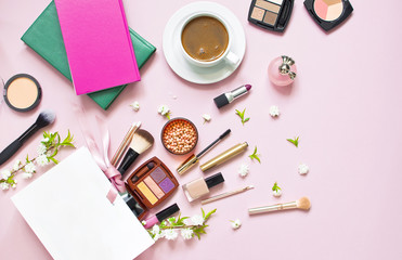 Various cosmetic products for makeup and white spring flowers in a white gift bag, notepad, cup of coffee on a pink pastel background top view with copy space