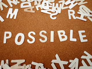 """""""Possible"""" writing with wooden letter on wood board background"""