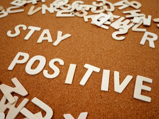 """Stay positive"" writing with wooden letter on wood board"