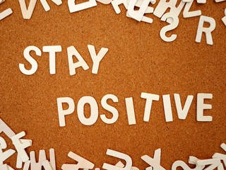 """Stay positive"" writing with wooden letter on wood board, top view"