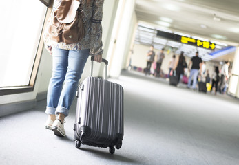 Woman tourist is traveling int he airport for departure.