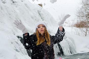 beautiful girl at the winter waterfall