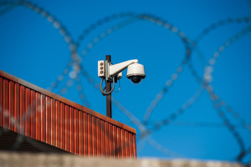 Close up view of security camera hanging among barbwire in prison or other guarded object with blue sky background. Modern ways of supervision. Using new technology in security and safety.