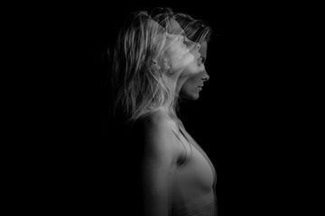 Beautiful fuzzy drama mystical mysterious ambiguous original conceptual profile side portrait of young blonde woman on a black background. Black and white photo. triple exposure.