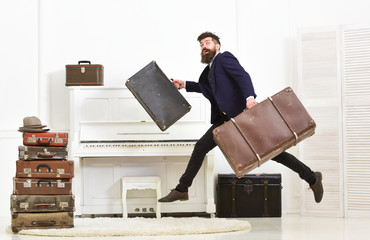 Butler and service concept. Man with beard and mustache in suit delivers luggage, luxury white interior background. Macho attractive, elegant on cheerful face carries vintage suitcases, jumping.