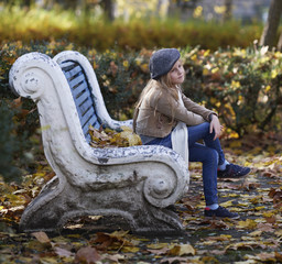 The girl is on the bench. Autumn and yellow leaves