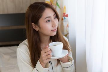 コーヒーを飲むパジャマの女性