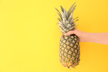 Woman holding fresh ripe pineapple on color background
