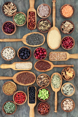 Healthy food concept with legumes, fruit, grains, cereals, medicinal herbs and spice. Foods high in omega 3 fatty acids, antioxidants, anthocyanins, minerals, vitamins and dietary fibre. Top view.