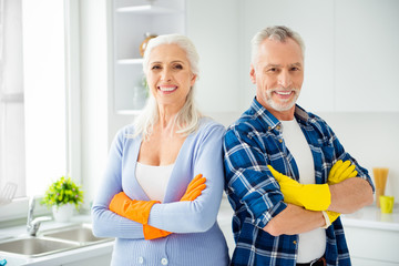 Lovely attractive cleanly neat cheerful stylish couple of senior in colorful gloves standing with crossed arms after cleaning, looking at camera, in the kitchen flat apartment