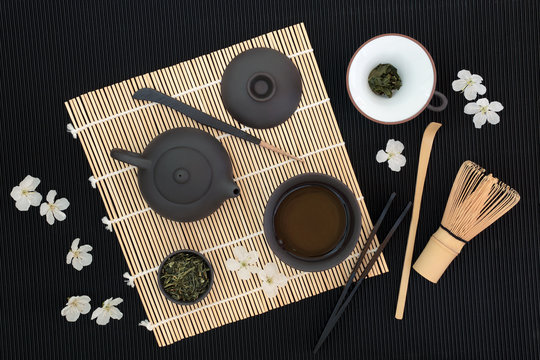 Sencha sukiygu makoto Japanese tea with teapot and cup, dried leaves, whisk, strainer, scoop, stick stirrer, tongs  and spring blossom on bamboo and black ridged background.