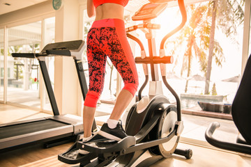 Sportgirl exercise on elliptical cross trainer at gym