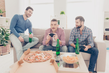 Three attractive handsome stylish men in casual outfits playing videogame, laughing from frustrated upset loser sitting in living room, drinking  beer, lager from bottle, having pizza, chips