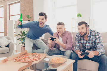 Portrait of stylish attractive modern successful three men in casual outfits playing video game holding joystick in hands, having snack, pizza, chips, good, alcohol beverages on the table