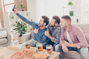 Portrait of stylish, attractive, modern positive guys sitting in livingroom, having pizza, beer, chips on the table, shooting selfie on smart phone, showing thumb up, enjoying soccer word cup