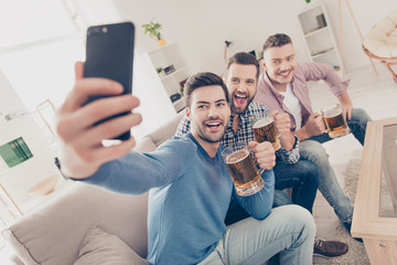 Stylish, attractive, modern positive guys sitting in living room, having mugs with lager in hands, shooting selfie on smart phone, shouting, screaming, enjoying sport football competition