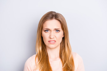 Close up portrait of funny confused puzzled unhappy upset sad uncertain unsure beautiful pretty charming grimacing woman with long blonde hairdo isolated on gray background opy-space