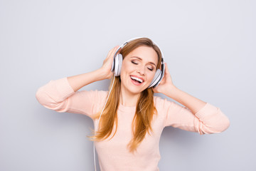 Weekend holiday day vacation day-off youth concept. Portrait of excited cheerful glad active beautiful lady enjoying favorite music isolated on gray background touching headphones copy-space