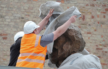 Workers cover the head of a bronze statue of Marx in Trier