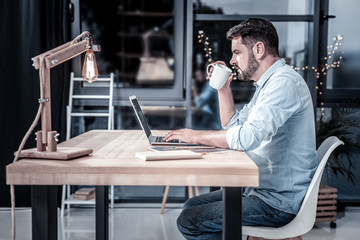 Do not distract. Serious busy unshaken man sitting by the table using the laptop and drinking tea.