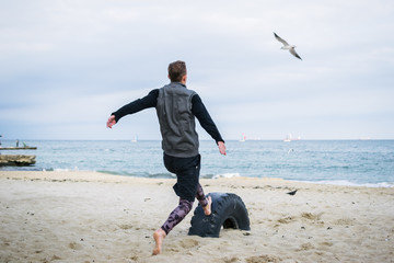 Young man doing parkour tricks on the beach near the sea