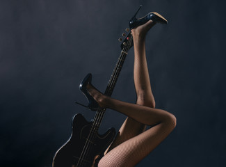 Electric guitar with legs. Sexy woman with electric guitar. Beautiful young sexy woman with guitar. Musical art sensual girl. Erotic music for sex. Musician and guitarist. Beautiful melody and body