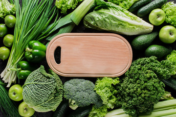 top view of cutting board between green vegetables, healthy eating concept