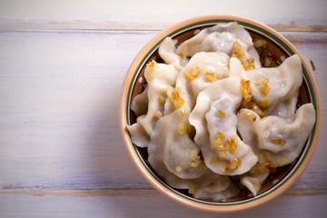 Pierogi or pyrohy, varenyky, vareniki, dumplings in bowl on wooden table. horizontal