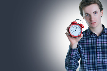 Close-up portrait of a troubled young man holding alarm clock isolated over grey background.