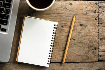 Top view of blank notebook with white coffee, laptop and with natural light on wooden table.