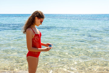 Happy woman with a photograph of the sea. A girl is making a photo with a clear sea
