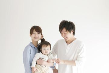 赤ちゃんを抱き微笑む夫婦