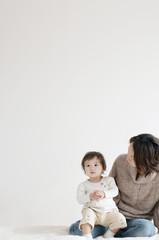 母親の膝に座る赤ちゃん