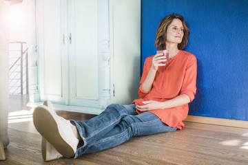 Relaxed woman sitting on the floor at home with healthy drink