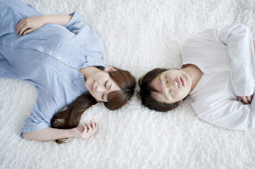 ラグの上で眠るカップル