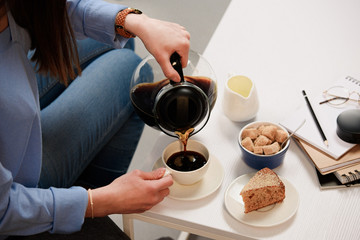 cropped shot of woman pouring coffee into cup with cane sugar and piece of cake on coffee table