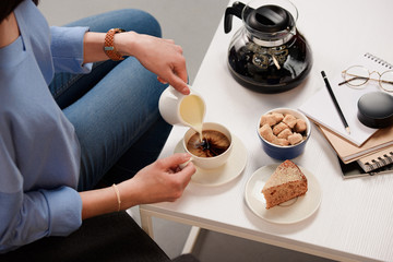 cropped shot of woman pouring cream into cup of coffee with cane sugar and piece of cake on coffee table