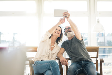 Happy mature couple sitting on chairs at home using tablet